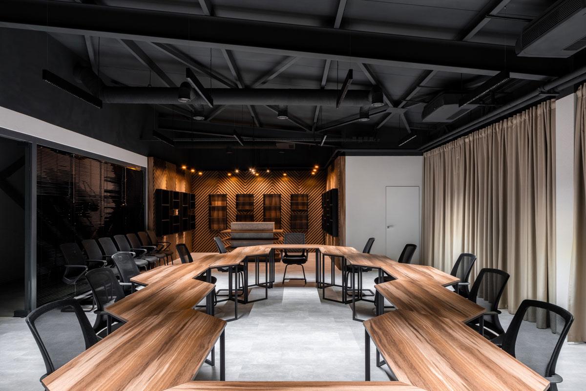 Sala de conferinta la oficiu Sapico. Amenajare de interior cu elemente din lemn so birouri asezate ordonat.