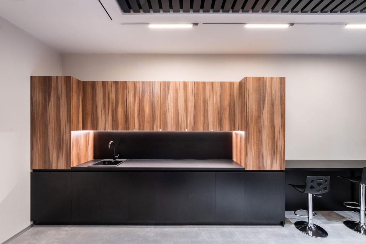 Amenajare bucatarie in oficiu Sapico, cu elemente din lemn si spatiu pentru pastrarea produselor si aparatelor de cafea. Design de la biroul ab+partners