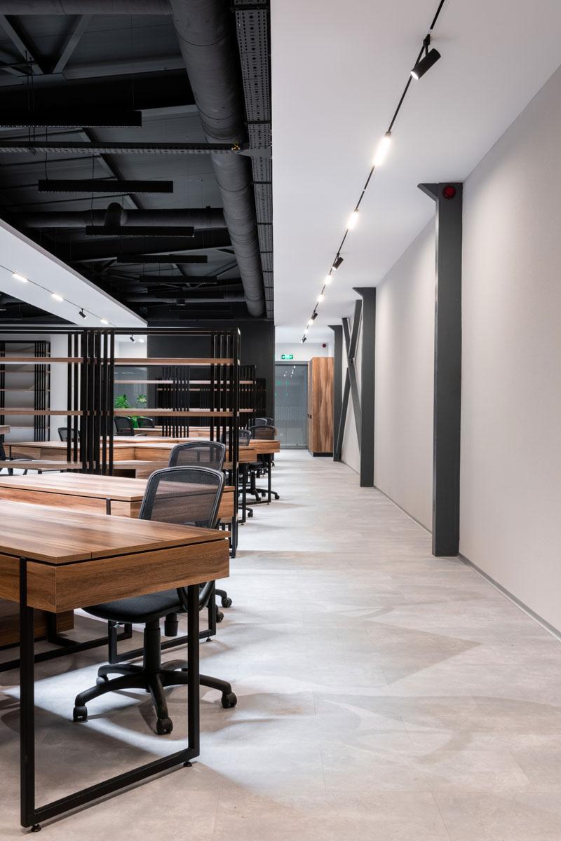 Oficiu open space Sapico, cu birouri asezate ordonat, in culori negru si gri. Proiect ab+partners